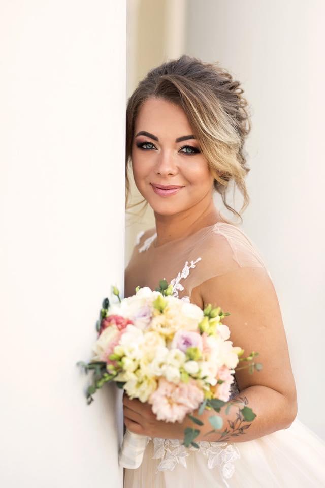makijaż ślubny Wrocław i sesja zdjęciowa przedstawiająca młodą kobietę trzymającą w dłoni kwiaty