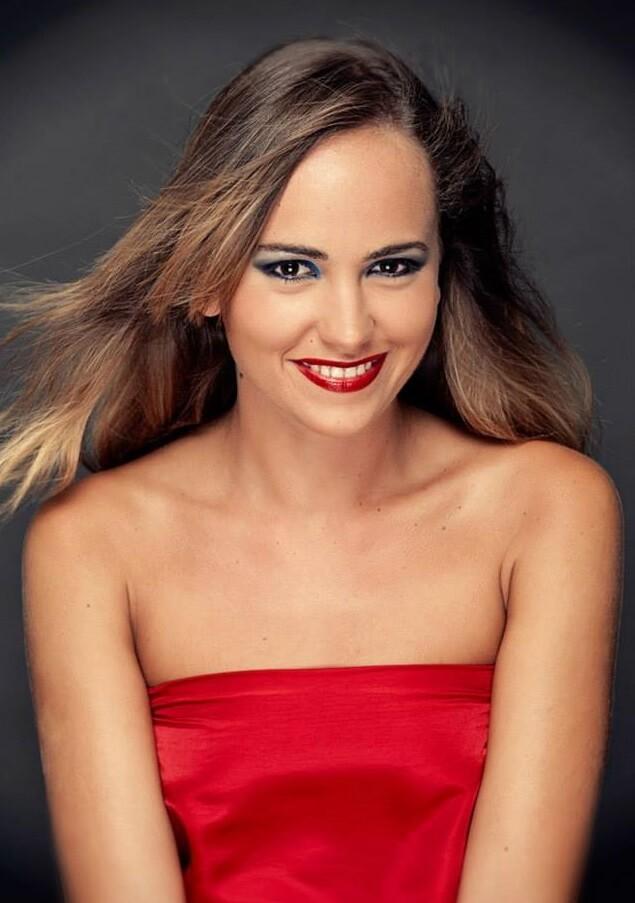 makijaż do sesji zdjęciowej wykonany we Wrocławiu. Kobieta w czerwonej sukni i rozwianą fryzurą