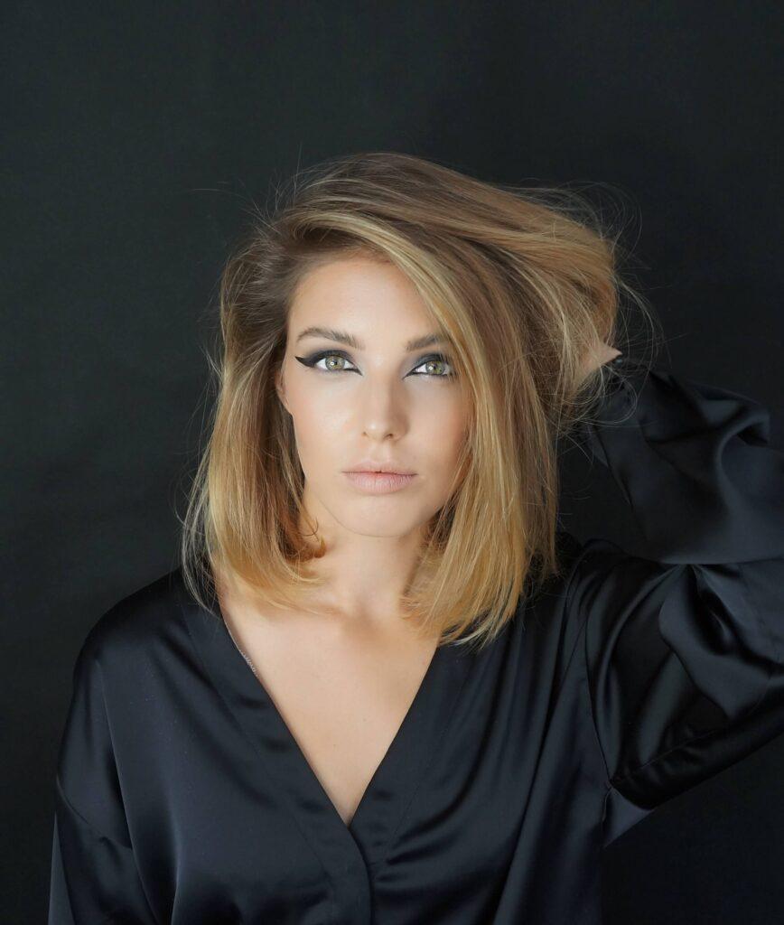 Przykład makijażu do sesji fotograficznej. Kobieta we Wrocławiu, ubrana w czerń pozująca fotografowi
