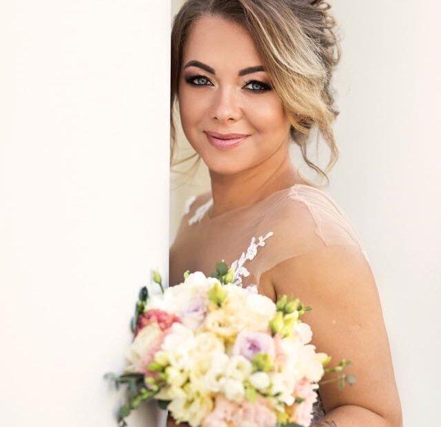 makeup Pani Młodej przy okazji sesji zdjęciowej ślubnej. Blondynka w kreacji weselnej, w ręku trzyma kwiaty